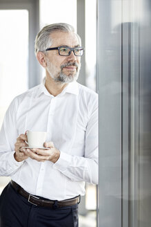 Businessman with cup of coffee looking out of window - RBF06344