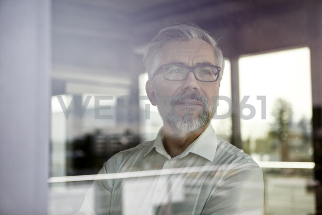 Portrait of businessman looking out of window - RBF06347