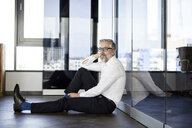 Businessman sitting on the floor in office - RBF06350