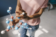 Female scientist holding molecule model - KNSF04059