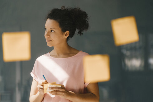 Woman brainstorming in office usine adhesive notes - KNSF04062