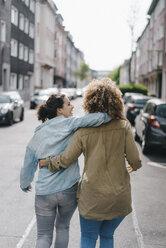 Best friends walking in the city, arm in arm, rear view - KNSF04119