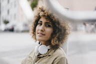 Woman in the city with headphones, portrait - KNSF04137