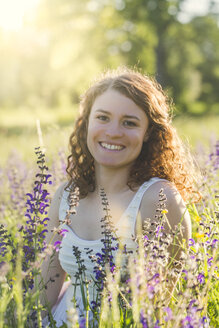 Young woman sitting on summer meadow - SARF03809