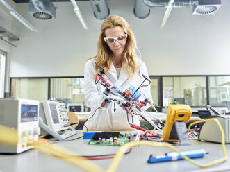 Female technician working in research laboratory, developing drone - CVF00875