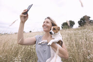 Woman with dog taking selfie with smartphone on a field - KMKF00393
