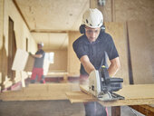 Worker with helmet sawing wood with circular saw - CVF00899