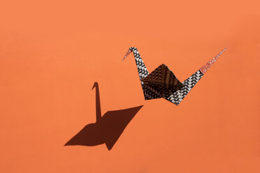 Origami crane, orange background, shadow, copy space - PSTF00136