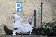Origami dog in front of concrete wall, parking sign - PSTF00151