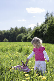 Little girl with origami rabbit on meadow - PSTF00163