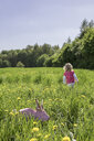Little girl and origami rabbit on meadow - PSTF00166