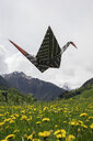 Origami crane flying over meadow - PSTF00169