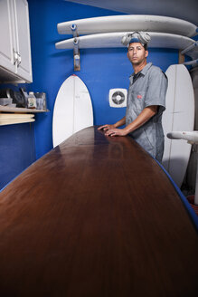 Portrait of a mid adult man and surfboard in his workshop - CUF34523