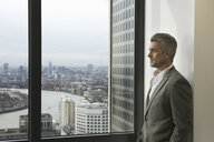 Portrait of mature businessman looking out of office window, Canary Wharf, London, UK - CUF34586