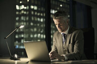 Businessman working late in office on laptop - CUF34589