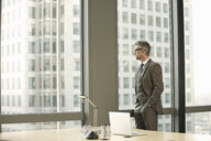 Businessman looking out of office window - CUF34595