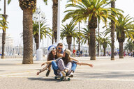 Carefree friends having fun with a skateboard on a promenade with palms - WPEF00449