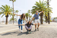 Carefree friends having fun with a skateboard on a promenade with palms - WPEF00452