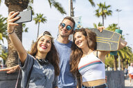 Three happy friends with skateboard taking a selfie - WPEF00455