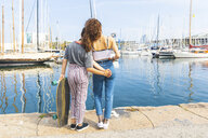 Young woman and teenage girl with a skateboard standing at marina - WPEF00461