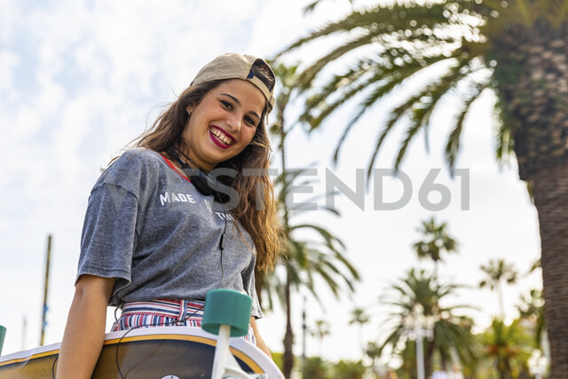 Portrait of happy teenage girl with skateboard on a promenade with palms - WPEF00464