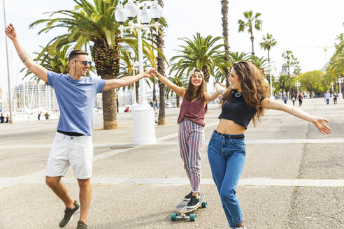 Carefree friends having fun with a skateboard on a promenade with palms - WPEF00470