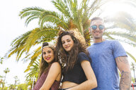 Portrait of smiling friends at a palm tree - WPEF00473
