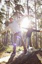 Twin brothers walking along fallen tree trunk in forest - CUF34638