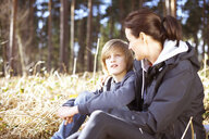 Mature woman taking a break with her son in a forest - CUF34650