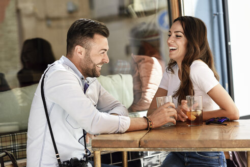Happy couple having a drink at an outdoor bar in the city - JSMF00302