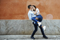Carefree couple in love in front of a wall outdoors - JSMF00308