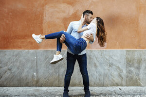 Carefree couple in love kissing in front of a wall outdoors - JSMF00311