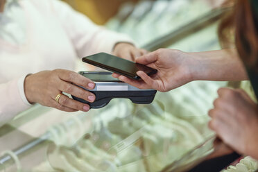 Close-up of woman paying with smartphone in a store - JSMF00335
