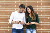 Couple looking at their smartphones at a brick wall - JSMF00338