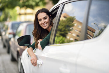 Smiling young woman leaning out the window of her car in the city - JSMF00341