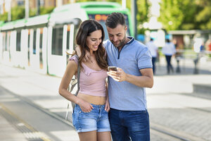 Couple looking at smartphone while waiting for tram at the station - JSMF00344