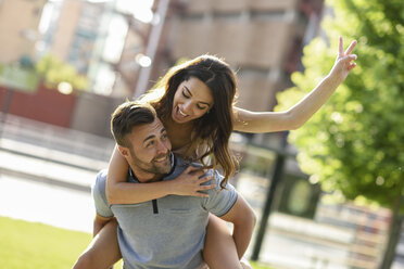 Happy man giving girlfriend a piggyback ride in park - JSMF00350