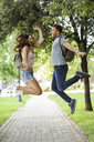 Carefree couple jumping in park - JSMF00353
