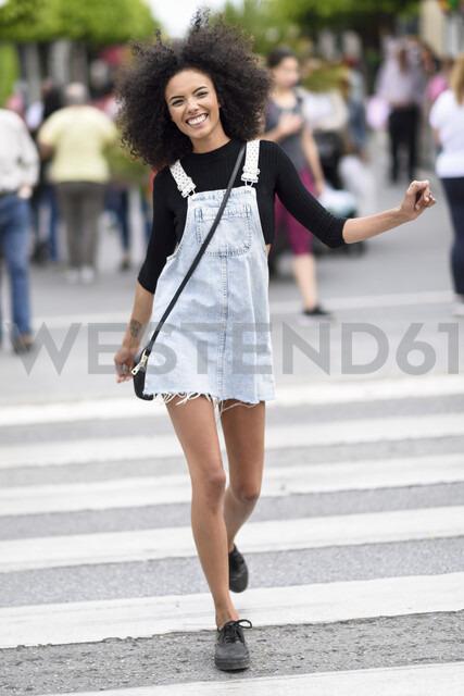 Portrait of happy young woman walking on zebra crossing - JSMF00365