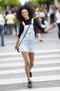 Portrait of happy young woman walking on zebra crossing - JSMF00365