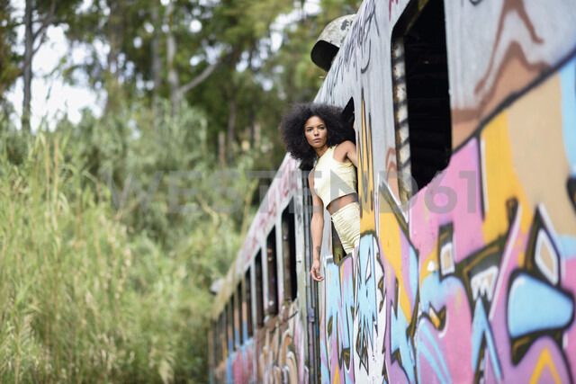 Fashionable young woman leaning out of window of an abandoned and destroyed old train - JSMF00377