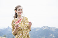Mid adult woman with watermelon, Wallberg, Tegernsee, Bavaria, Germany - CUF34744