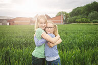 Portrait of nine year old girl and sister hugging in field - CUF34753