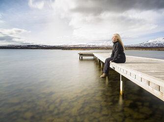 Mid adult woman gazing from pier, Thingvellir, Iceland - CUF34825