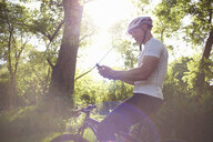 Cyclist using smartphone in forest - CUF34867
