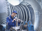 Engineer at workstation in front of steam turbine - CUF34969