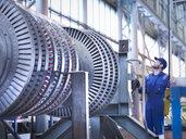 Engineer lifting high pressure steam turbine with crane in workshop - CUF34975