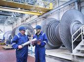 Engineers discussing rotor blade in turbine repair workshop - CUF34978