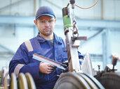 Portrait of engineer fitting blades to steam turbine in repair works - CUF34984