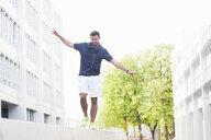 Jogger balancing on low wall - CUF35110